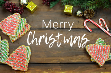 Christmas tree shaped sugar cookies, candy canes pine branches with cones, mini gifts and jingle bells on a wide-plank rustic wooden background. Text added.