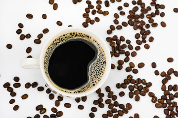 A photo of black aromatic coffee with froth in a white mug among coffee beans in defocusing on a white background. View from above