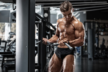 Muscular man workout in gym doing exercises for biceps, strong male naked torso abs Fototapete