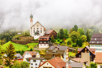 Wall Mural - Wassen Alpine village in Switzerland. Beautiful autumn scenery of classical Swiss countryside with church and traditional houses among yellow-green foliage trees. Seasonal autumnal landscape with fog.