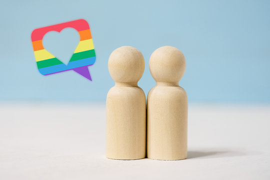 Pair of wooden figures in love stand close together.