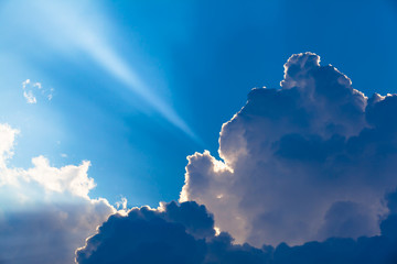 Heavenly Beam of Light / Small ray of sunlight up to blue sky behind dark clouds  (copy space)