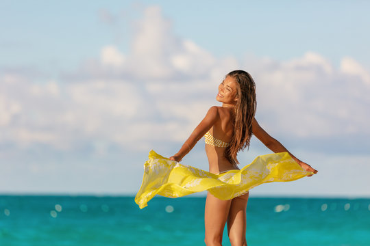 Swim beach model Asian woman carefree with cover up sarong scarf free in the wind enjoying sunset vacation Caribbean travel. Summer bikini body tan and hair removal spa concept.