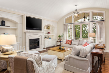 Beautiful living room in new traditional style luxury home. Features vaulted ceilings, fireplace with wall mounted tv, french doors leading outside, and elegant furnishings.