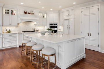 Beautiful kitchen in new traditional style luxury home, with large island, double ovens, cook top, and open concept floor plan