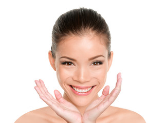 Happy beauty Asian woman showing perfect glowing dewy skin. Facial treatment skincare beautiful mixed race Eurasian model with hands under face.