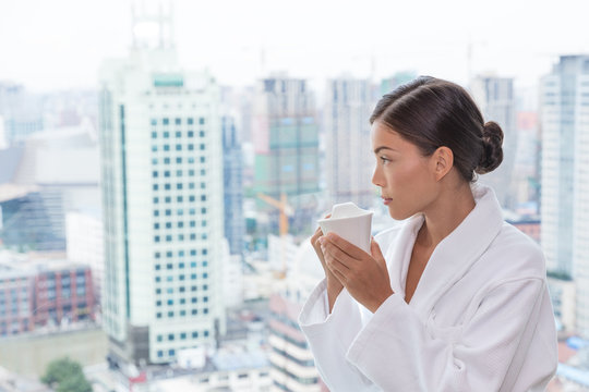 Asian woman in pampering spa resort luxury hotel drinking tea relaxing wearing bathrobe looking at view from bedroom window. Asian travel lady enjoying room service.