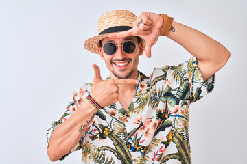 Young handsome man wearing Hawaiian shirt and summer hat over isolated background smiling making frame with hands and fingers with happy face. Creativity and photography concept.