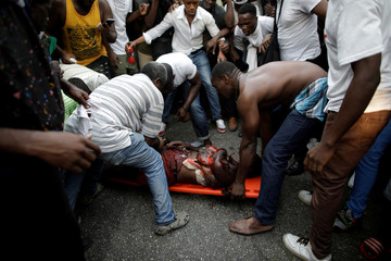 Men evacuate an injured woman hit by a truck taking part in the march that crashed with attendees during a demonstration to demand the resignation of Haitian President Jovenel Moise, in the streets of Petion Ville, Port-au-Prince