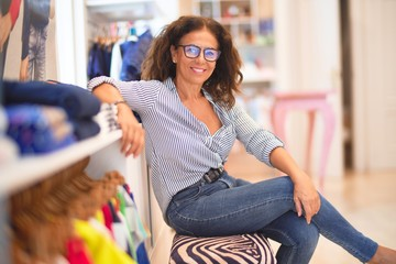 Middle age beautiful businesswoman wearing striped shirt and glasses smiling happy and confident...