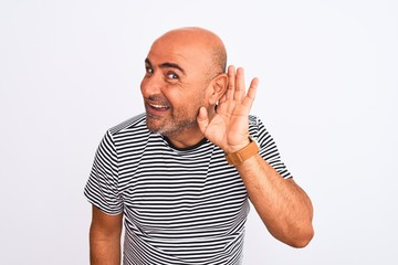 Middle age handsome man wearing striped navy t-shirt over isolated white background smiling with hand over ear listening an hearing to rumor or gossip. Deafness concept.