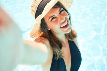 Young beautiful and sexy woman at the hotel pool taking a selfie smiling using smartphone on sunny day