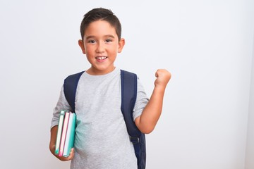 Beautiful student kid boy wearing backpack holding books over isolated white background screaming proud and celebrating victory and success very excited, cheering emotion