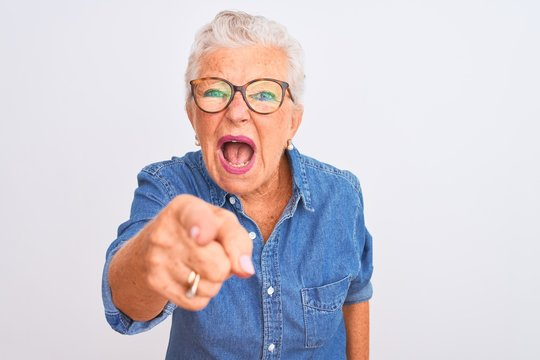 Senior grey-haired woman wearing denim shirt and glasses over isolated white background pointing displeased and frustrated to the camera, angry and furious with you
