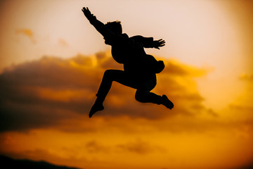 Athletic silhouette dancer while doing modern dance while jumping