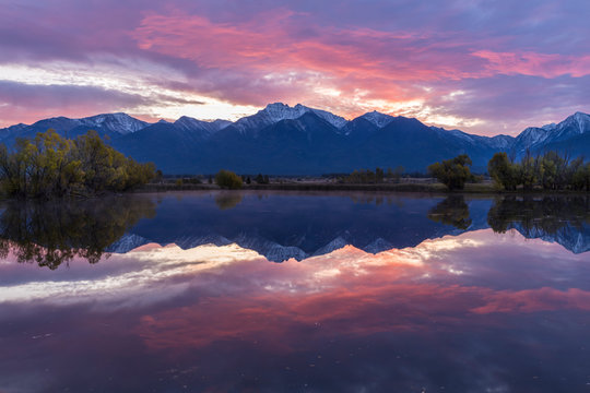 Red skies reflect in the calm pond near St. Ignatius, Montana.