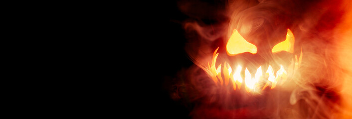 Scary Halloween jack o lantern face glowing in smoke and fire with blank copy space for text.