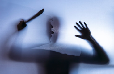 A man is armed with a knife. His shadow can be seen behind a curtain. Concept: crime