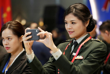 A Thai military personnel takes a picture at the Xiangshan Forum in Beijing