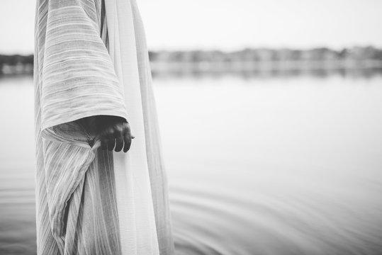 Closeup shot of a person wearing a biblical robe while standing in the water in black and white