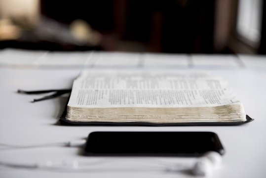 Closeup shot of an open bible near a smartphone with a blurred background