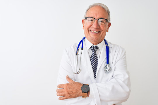 Senior grey-haired doctor man wearing stethoscope standing over isolated white background happy face smiling with crossed arms looking at the camera. Positive person.
