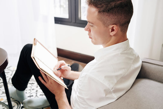 Handsome young man in white shirt sitting on the floor in living room and writing down thoughts and creative ideas in planner