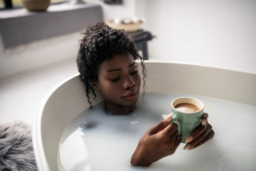 Woman having perfect morning while drinking coffee lying in bath
