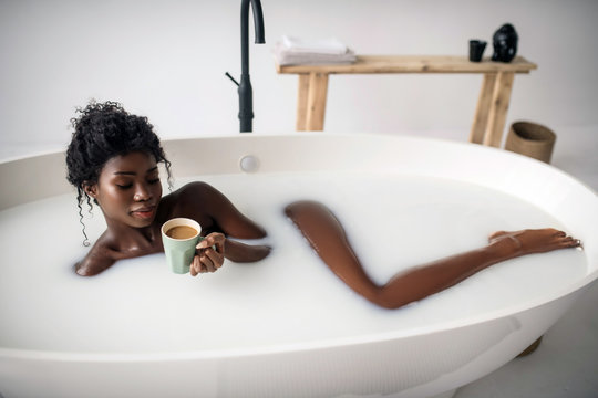 Curly woman chilling in bath and drinking coffee with milk