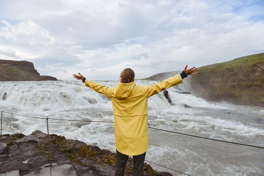 Beautiful scenery nature landscape with young travelling woman in yellow coat  near the waterfall, Iceland
