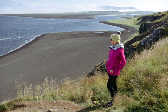Adventure traveller woman visiting nature landscape in summer near the ocean,  wearing  hat and colorful coat. Trip to  Iceland
