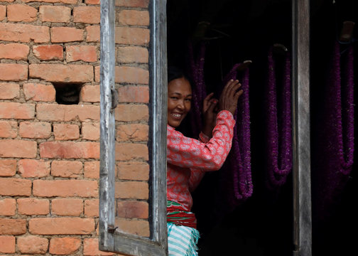 A woman smiles as she arranges garland made of globe amaranth flowers, before selling them to the market for the Tihar festival, also called Diwali, in Bhaktapur