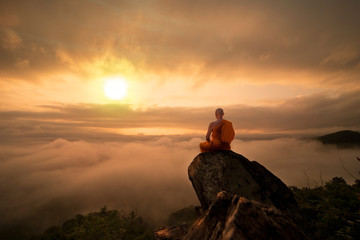 Zelfklevend Fotobehang Zonsondergang Buddhist monk in meditation at beautiful sunset or sunrise background on high mountain