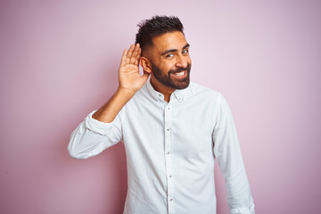 Fototapeta Young indian businessman wearing elegant shirt standing over isolated pink background smiling with hand over ear listening an hearing to rumor or gossip. Deafness concept.