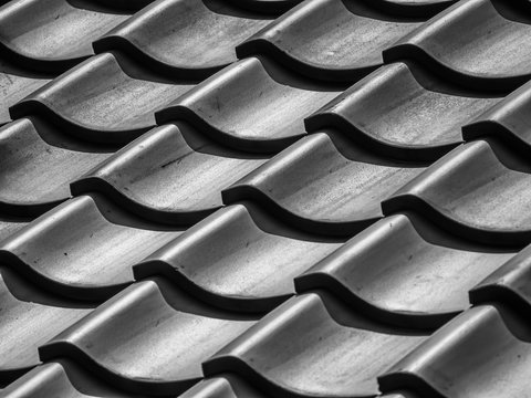 Abstract black and white tone background. Grids pattern of ceramic roof tiles texture with light and shadow from sunlight.