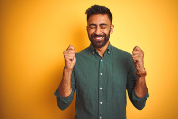 Young indian businessman wearing elegant shirt standing over isolated white background excited for success with arms raised and eyes closed celebrating victory smiling. Winner concept.