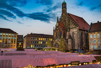 Nuremberg, Germany - December 2018: View of christmas market with historic cathedral called Frauenkirche, famous landmark of Nuremberg, Franconia, Bavaria