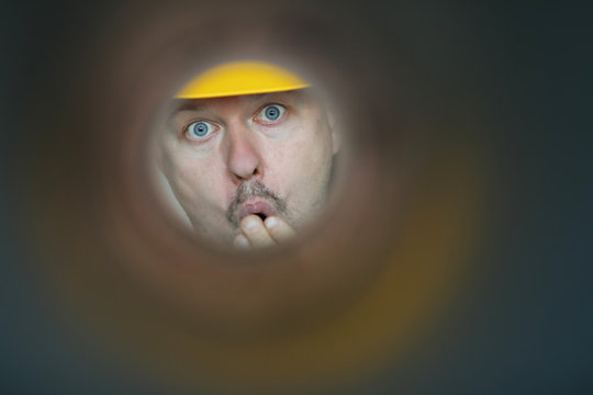 Male plumber looks into contaminated pipe