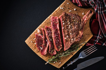 Entrecote. Steak on the bone. Rib eye. Tomahawk steak on the on a cutting board with rosemary. Roasting - Rare
