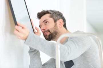 man hanging blank picture frame on wall