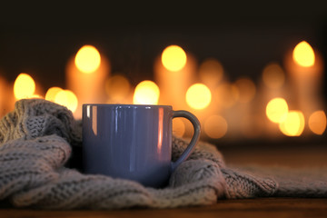 Cup of hot drink and knitted cloth against blurred background. Winter atmosphere