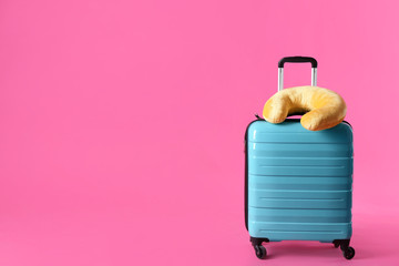 Turquoise suitcase and travel pillow on pink background, space for text