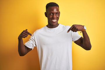 Young african american man wearing white t-shirt standing over isolated yellow background looking confident with smile on face, pointing oneself with fingers proud and happy.