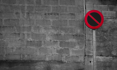 No parking sign. Regulatory sign. Circle red and black no parking sign on post. Traffic sign on gray and white brick wall texture background. Road signs for prohibit car parking. Restrictive signs.