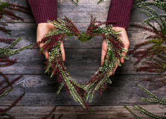 Hands making flower wreath of pink and white heath blossoms in heart shape on girl's hands. Home decoration. Top view.