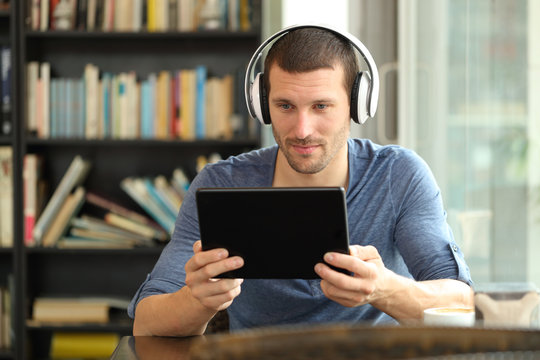 Serious man using tablet and headphones in a coffee shop