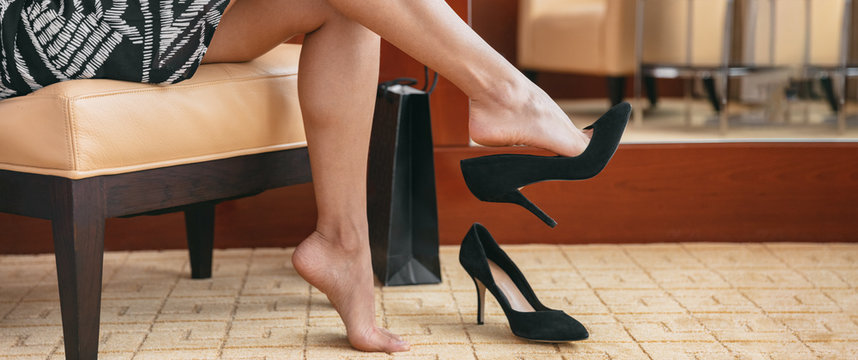 Foot pain woman taking off shoes after work day tired coming home removing high heels relaxing in sofa for the weekend. Luxury hotel room relax getaway. Feet health problem businesswoman.