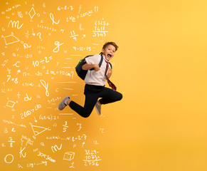 Young boy student runs fast to escape from school. Yellow background