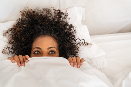 Funny black woman hiding under blanket