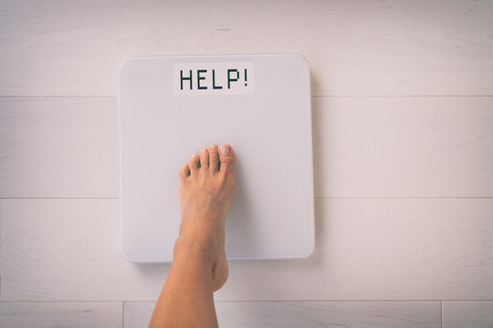 HELP weight loss scale woman foot stepping on balance. Screen showing text for trouble losing weight needing help of a nutrition professional dietitian for healthy advice.